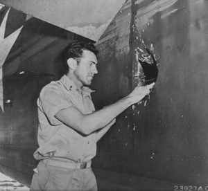 Zamperini examines a hole in his B-24D Liberator Super Man made by a 20mm shell over Nauru. (Public domain via Wikipedia.)